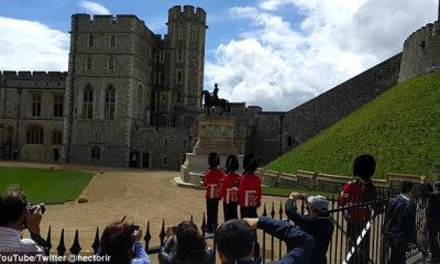 'Make way for the Queen's guard!': Guardsman shouts warning and then shoves a tourist out of his way after she tries to get a selfie with him in the background