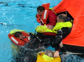 Two people in water with two other people in liferaft