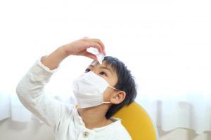 花粉症で目薬をさす子供