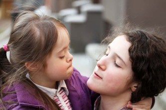 a young woman and young girl with down syndromemake faces at each other