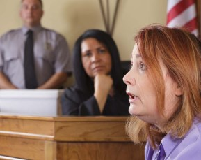 A witness with red hair gives testimony while a judge and law officer watch in the background.