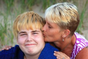 White woman kisses her teenage son with a disability on the cheek.