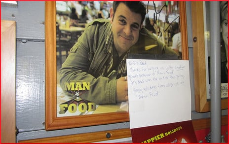 [photo of Adam Richman on a restaurant wall]
