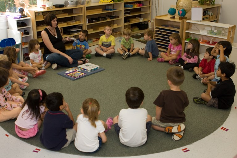 A teacher leads circle time. Difference between Montessori and Traditional Preschool.