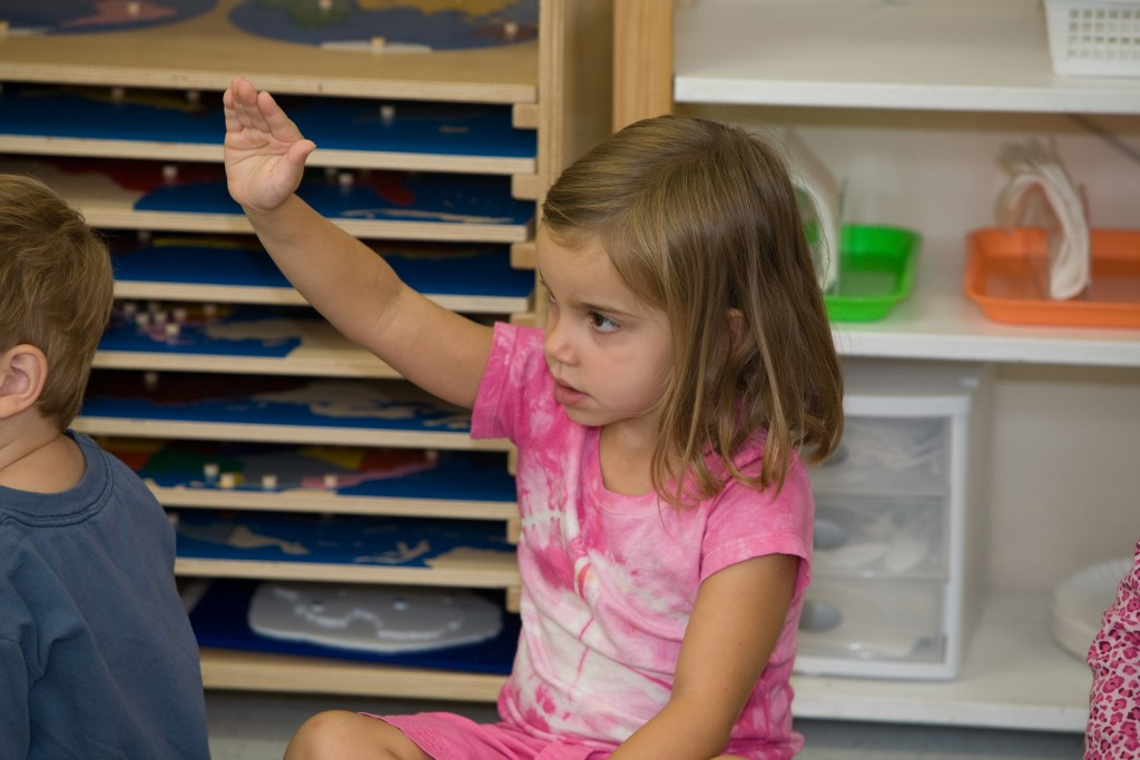 Child raises her hand at circle time at Children's House Montessori School of Reston.