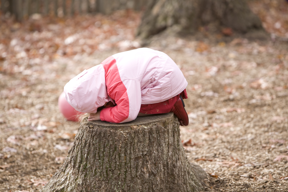 Child curled up on a tree stump, hiding. Imagination and Montessori
