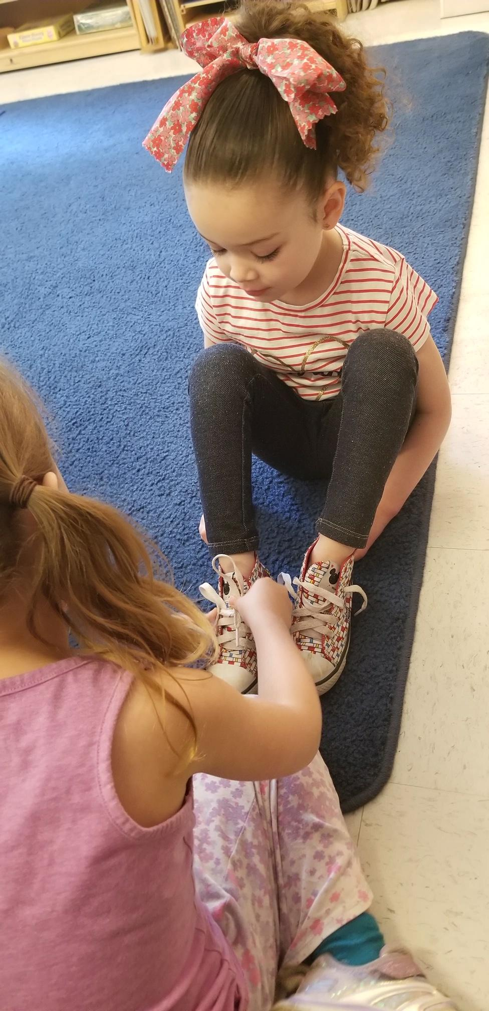 benefits of a mixed age classroom: a child helps another tie her shoes