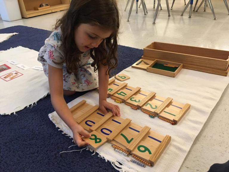 A child works with math materials. Difference between Montessori and traditional preschool.