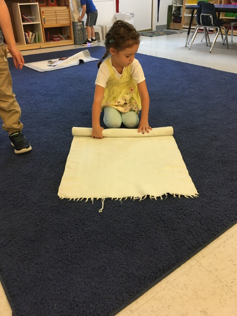 A child rolls a work rug. Teaching character development in early childhood.