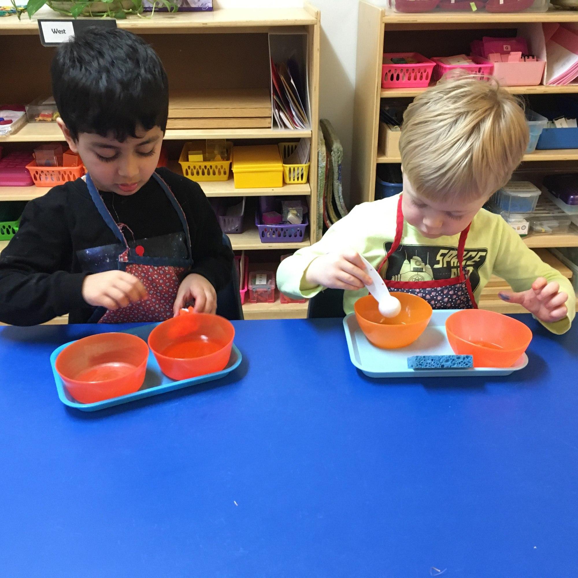 Two children using pouring materials at Children's House Montessori school.