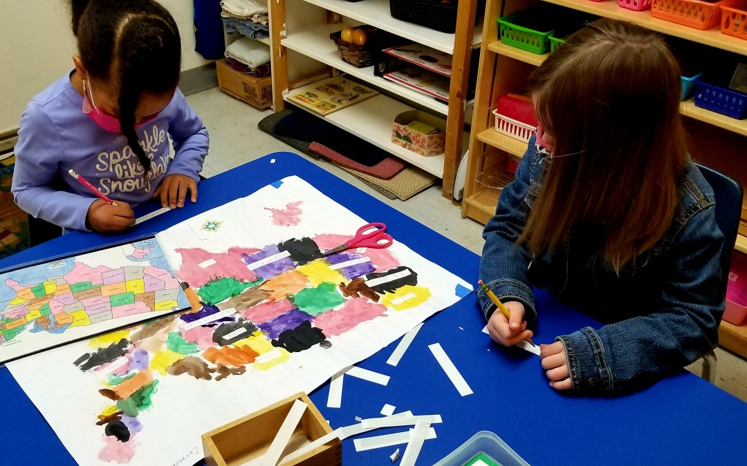 Two children working on a map of the USA. Children's House Montessori School of Reston