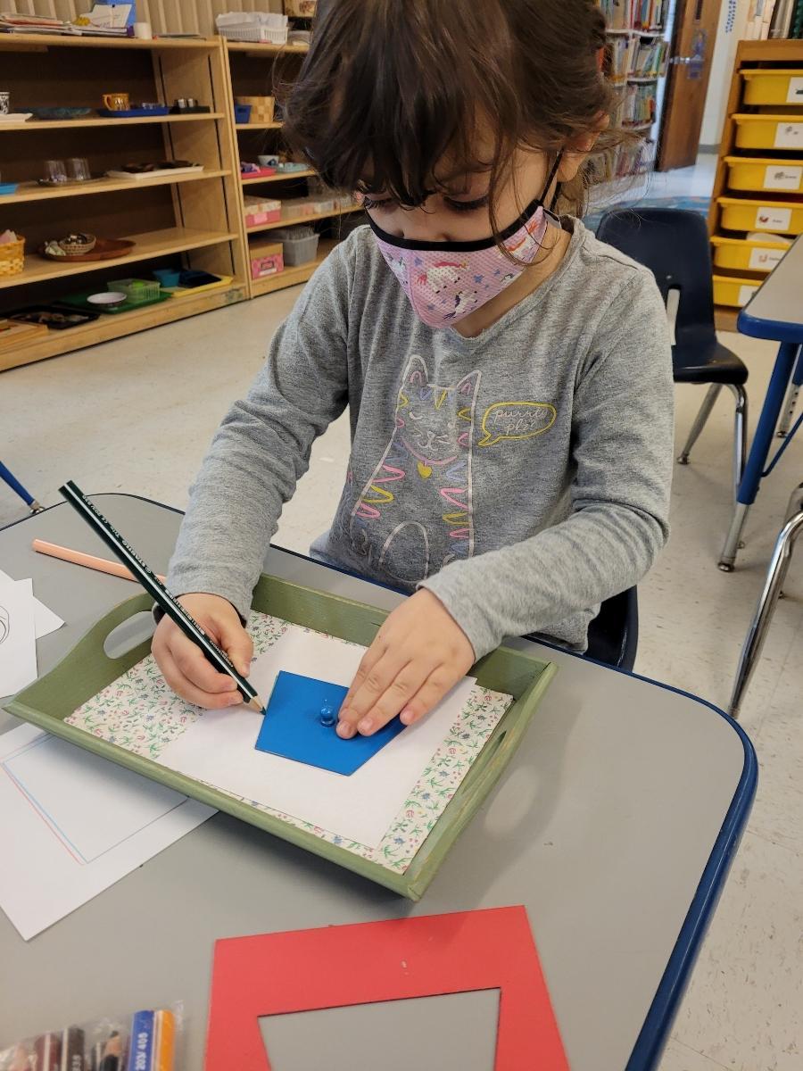 "child using Montessori Metal Insets from post ""How do Montessori Schools Teach Reading"""