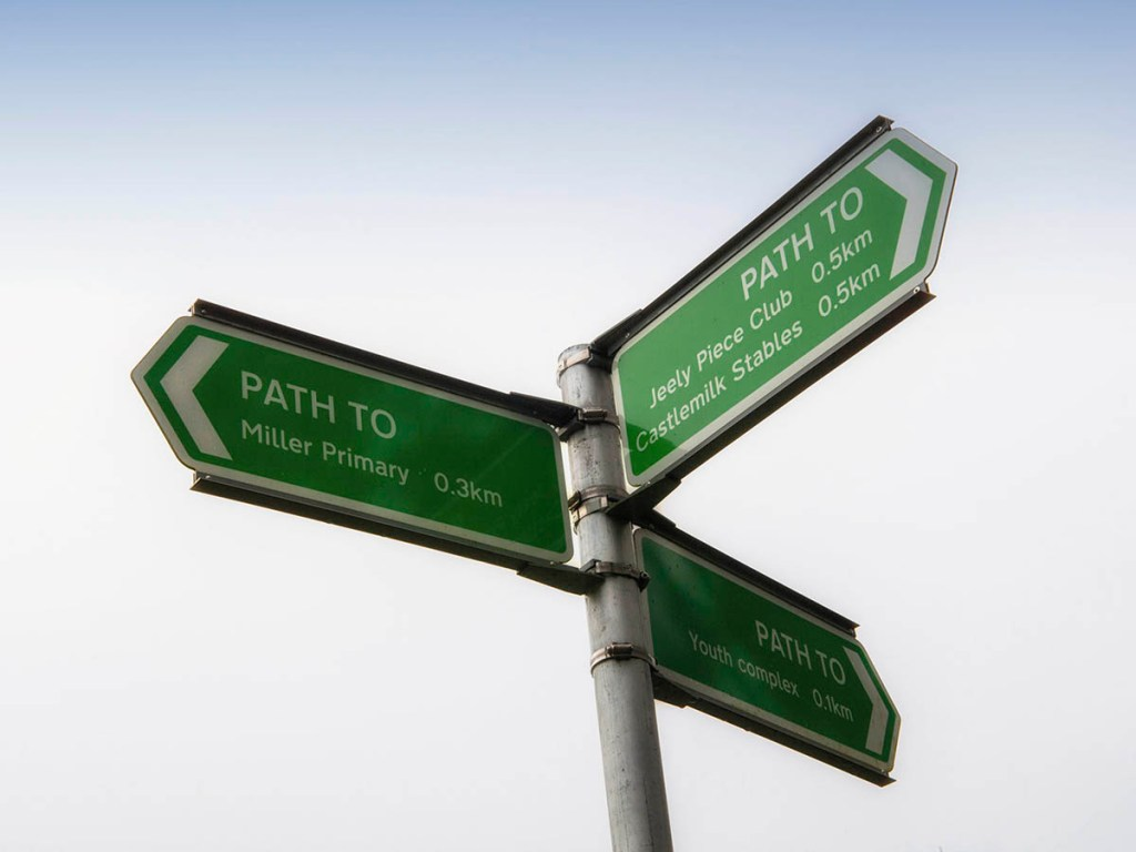A green signpost pointing in three directions