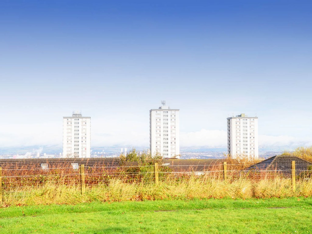 A view of three blocks of flats against a blue sky with grass in the foreground