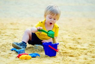 Toddler plays sand