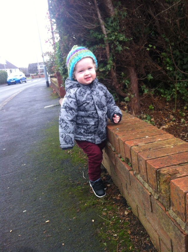 Living arrows. Lucas standing against a wall wearing a stripy knitted hat, grey and black robot print jacket, black nike trainers and maroon jeans