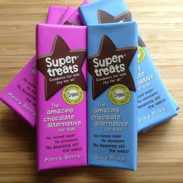 Supertreats review silky milky chocolate in blue wrapper and berry merry chocolate in pink wrapper on a wooden chopping board