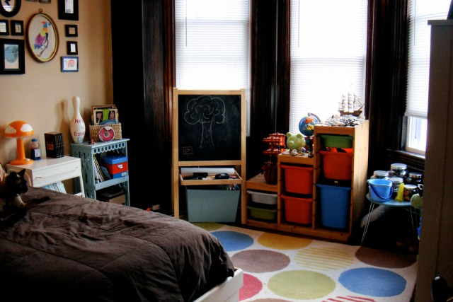 Choosing the perfect rug for your child's playroom A bedroom with a bed showing brown bedding, a colourful spotted rug on the floor, a child's chalkboard standing up and toys around the room