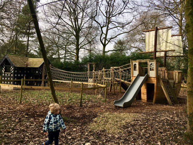 Samlesbury Hall, Preston. Lucas is stood in front of a wooden play area