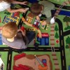 Choosing the perfect rug for your childs playroom Two boys playing on a large rug that has the design of a road to play with cars on