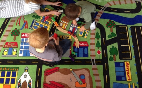 Choosing the perfect rug for your child's playroom Two boys playing on a large rug that has the design of a road to play with cars on