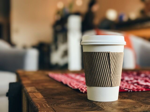 Save money long term. A photo of a takeaway coffee cup on a wooden table