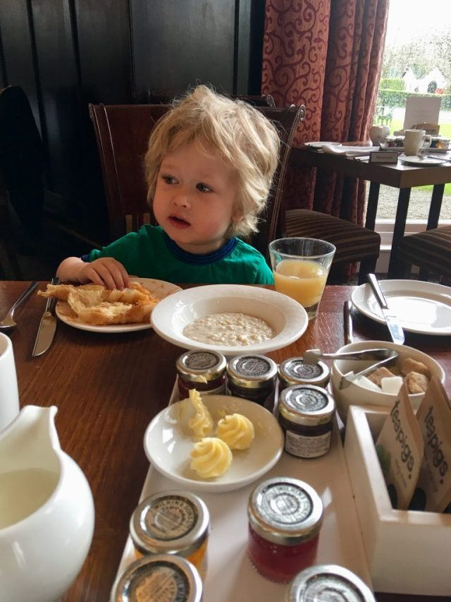 Low Wood Bay, Windermere review Lucas is sat a wooden table wearing a blue and green Tshirt. He has blonde messy hair. He is looking away from the camera. In front of him is a crossaint on his plate that his hand is touching. Before that is a milk jug and condiments