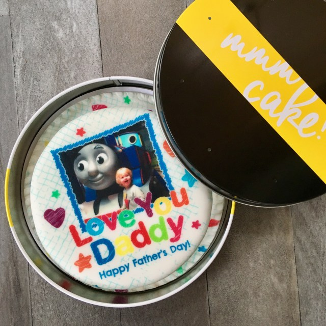 Father's Day gift ideas a photo of a circular baker days cake in a tin. The cake has colourful writing saying happy father's day and there is a photo of Lucas, a 3 year old blonde haired boy smiling at the camera next to thomas the tank engine