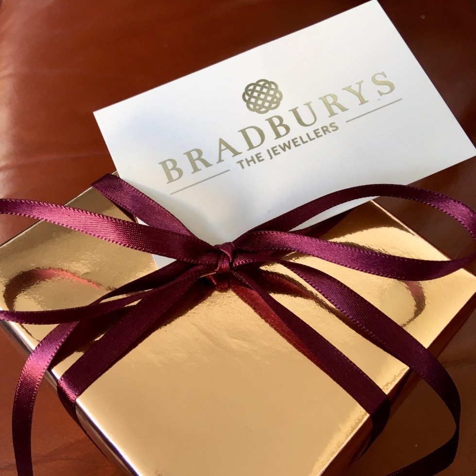 Bradbury's The Jewellers review. A gold gift wrapped box with burgundy ribbon tied round in bow with white and gold embossed business card