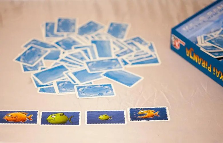 In der Mitte liegen die Spielkarten bunt gemischt mit der Bildseite nach unten. Vor dem Spieler liegen drei aufgedeckte Karten, auf denen Fische abgebildet sind.