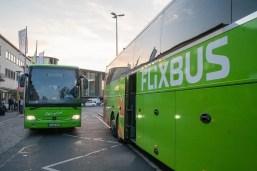 Zwei Flixbusse. Einer der Busse fährt auf den Fotografen zu.