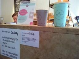 Auf der Theke stehen präsent die Becher. Stellenanzeige für Cafépersonal.