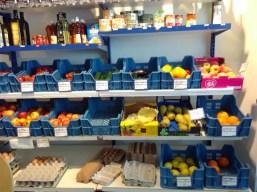 Angebot an Obst und Gemüse. Darüber stehen verschiedene Weine.