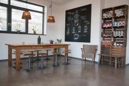 Ein Tisch mit Drehstühlen mitten im Raum, an der Wand eine große Tafel, ein gemütlicher Wohnzimmerstuhl und ein Regal mit Kaffeeprodukten