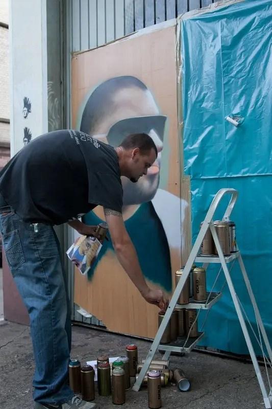 Sprayer sprüht ein Grafitti an die Garagentür