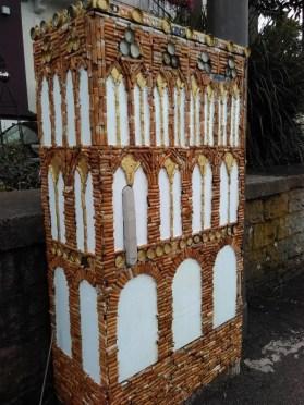 Mit Zigarettenkippen und Kronkorken gestalteter Stromkasten am Bismarckplatz.