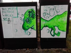 Ein schwarzer Stromkasten mit weißem Schild. Darauf ist ein grüner Dinosaurier gemalt.