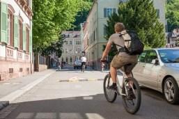 Theaterstraße mit zwei Radfahrern. Auf dem Boden ist ein Vorsicht-Schild mit spielenden Kindern aufgemalt und eine Bodenschwelle..