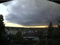 Bild der Webcam kurz vor dem Gewitter, Wolkenverhangener Himmel mit Sonnenuntergang im Hintergrund