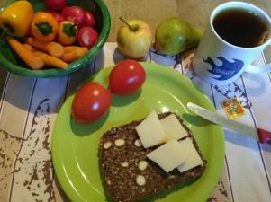 Blick auf das Frühstück mit verschiedenem Gemüse, Käse, Vollkornbrot und eine Literaturcamp-Tasse mit Tee