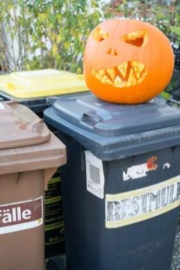 Verschiedene Hausabfalltonnen auf denen ein Halloweenkürbis grimmig schaut.