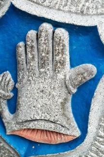 Blau-Silbernes Handschuh-Wappen in Stein.