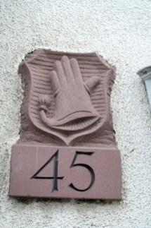 Steinplatte gemeißelt. Hausnummer 45 und Handschuh-Wappen.