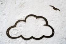 Eine Wolke und ein Vogel schematisch an einer Hauswand.