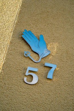 Handschuh und Hausnummer 57 aus Metall.