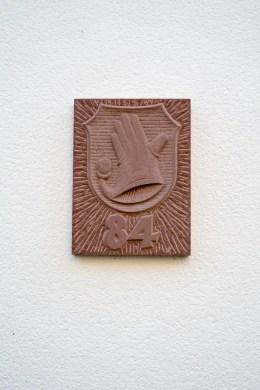 Steinplatte gemeißelt. Hausnummer 84 und Handschuh-Wappen.