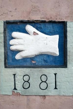 Handschuh in Weiß auf blauem Hintergrund und Jahreszahl 1881. Material Stein.