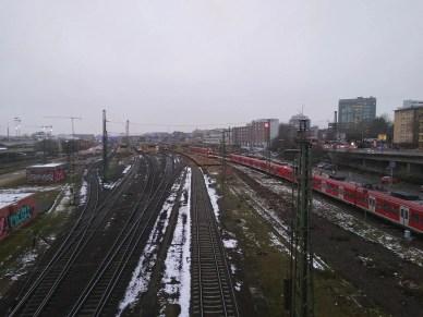 Blick auf den Heidelberger Hauptbahnhof von der Brücke. Gerade kommt eine S-Bahn.