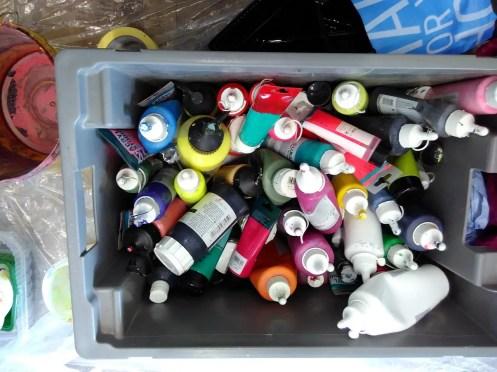 Kiste mit Acrylfarben von oben.