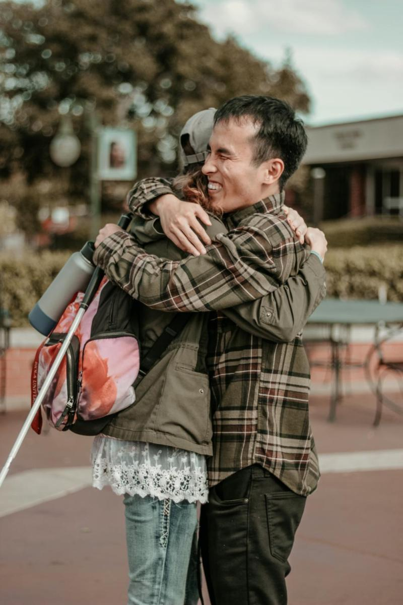 Photo features Senior, Music performance major David Chung embracing another student with a wide smile